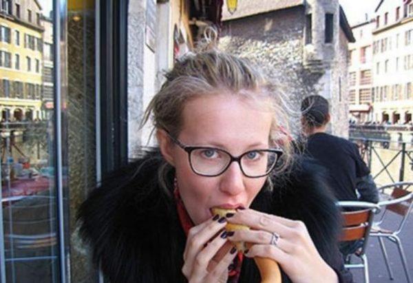 Ксения Собак ест сосиску