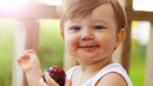 Ребенок ест сливу